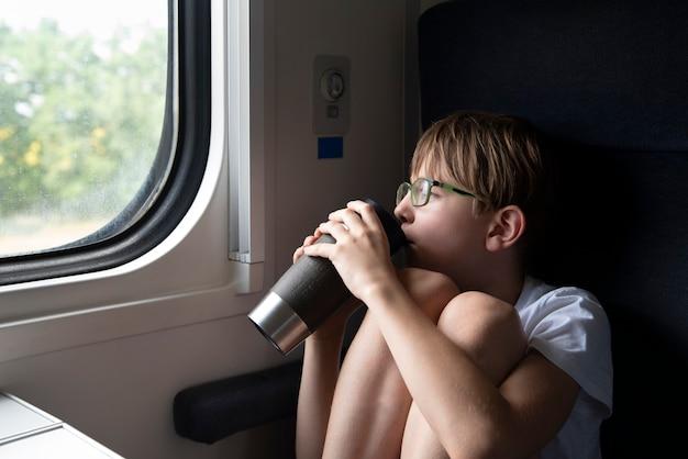 Criança na carruagem do compartimento está bebendo chá e olhando pela janela