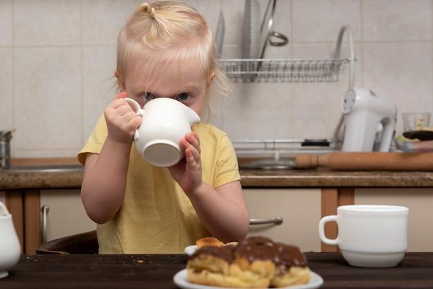 Criança na cozinha bebe do copo e olha para os bolos. café da manhã com criança. menina bebendo chá com massa.