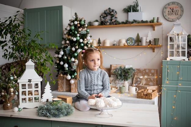 Criança na cozinha de manhã de natal em casa.