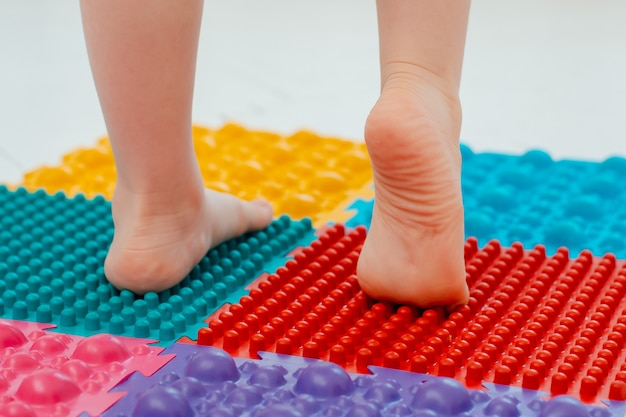 Criança na esteira de massagem do pé do bebê. exercícios para as pernas no tapete de massagem ortopédica. prevenção de pés chatos e hálux valgo