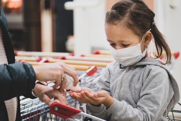 Criança na máscara protetora faz desinfecção das mãos com desinfetante em compras de supermercado