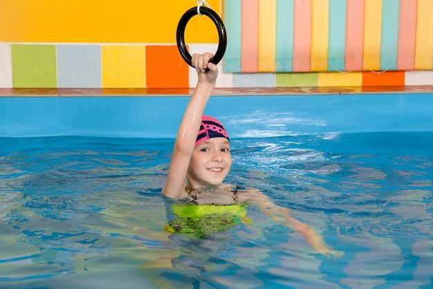 Criança na piscina excersizing com argolas esportivas