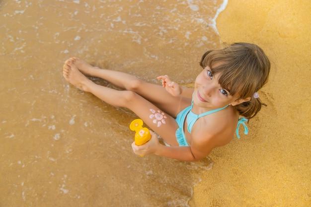 Criança na praia com protetor solar nas costas.