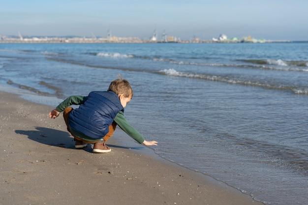 Criança na praia da praia brincando com as ondas