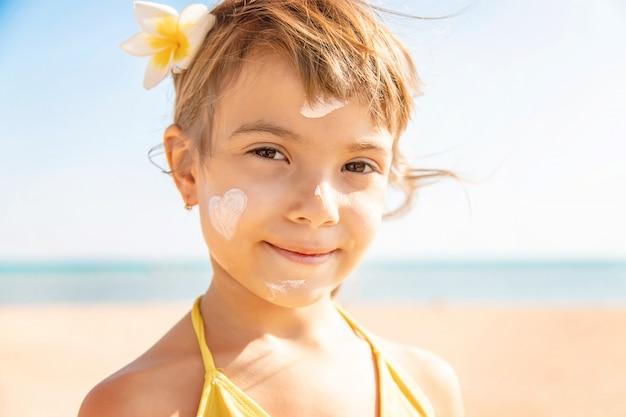 Criança na praia manchas protetor solar. foco seletivo.