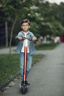 Criança na scooter de chute no parque. as crianças aprendem a patinar. garotinho patinando num dia ensolarado de verão.