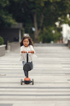 Criança na scooter de chute no parque. as crianças aprendem a patinar. menina patinando num dia ensolarado de verão.