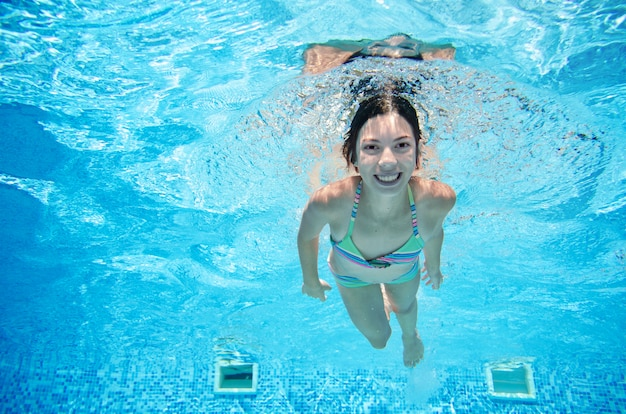 Criança nada na piscina debaixo d'água, feliz garota ativa em óculos se diverte na água, esporte de criança em férias em família