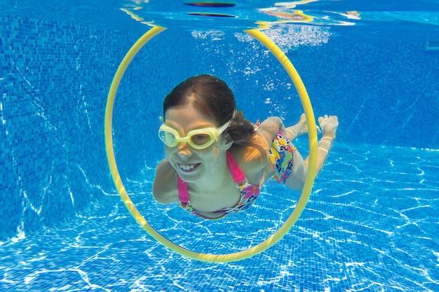 Criança nada na piscina debaixo d'água, feliz garota ativa mergulha e se diverte debaixo d'água, criança fitness e esporte em férias em família no resort