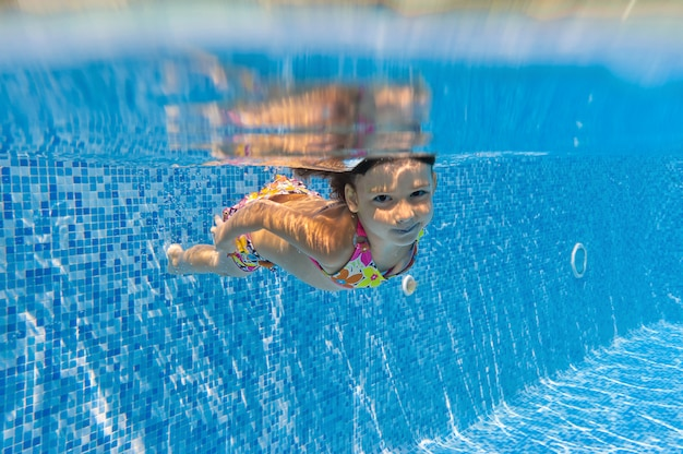 Criança nada na piscina debaixo d'água, feliz garota ativa mergulha e se diverte debaixo d'água, esporte de criança em férias em família