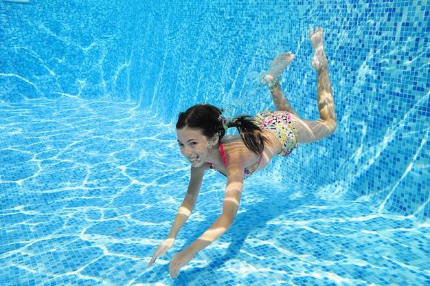 Criança nada na piscina debaixo d'água, feliz garota ativa mergulha e se diverte na água, criança fitness e esporte em férias em família