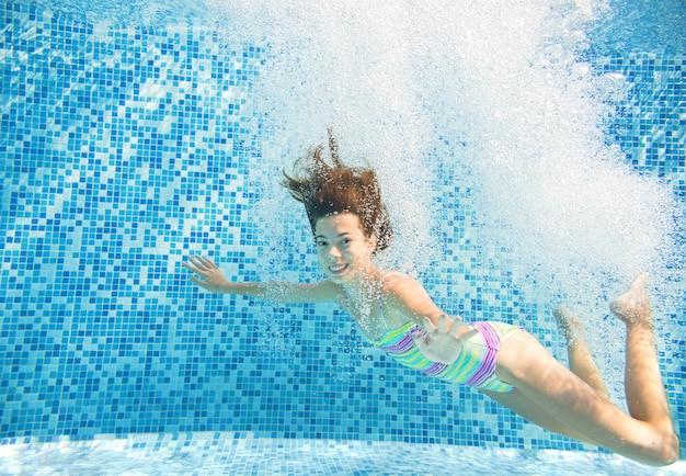 Criança nada na piscina debaixo d'água, feliz garota ativa salta, mergulha e se diverte debaixo d'água, crianças fitness e esporte em férias em família