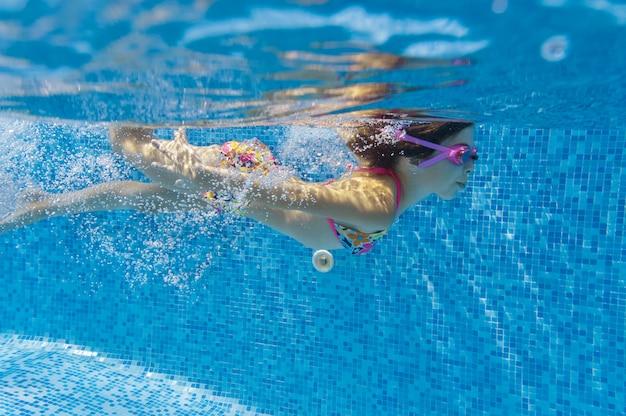 Criança nada na piscina debaixo d'água