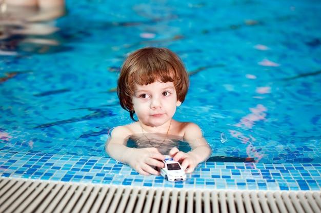 Criança nada na piscina