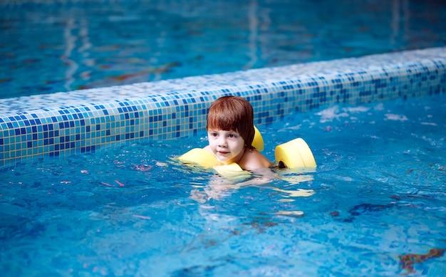 Criança nada na piscina.