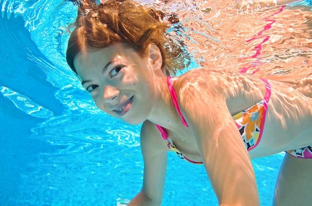 Criança nadando debaixo d'água na piscina, menina ativa mergulha e se diverte debaixo d'água