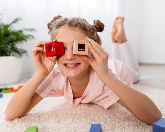 Criança não binária brincando com um jogo colorido em casa