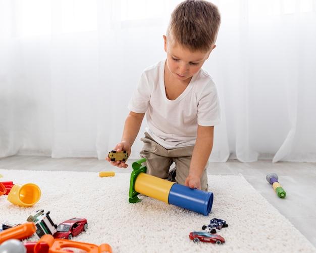 Criança não binária brincando com um jogo de carro