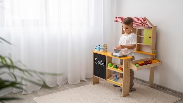 Criança não binária brincando dentro de casa com espaço de cópia
