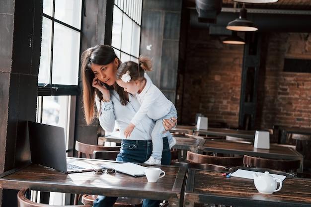 Criança não é problema para trabalhar. mulher de negócios com roupa oficial com criança está dentro de casa no café durante o dia.