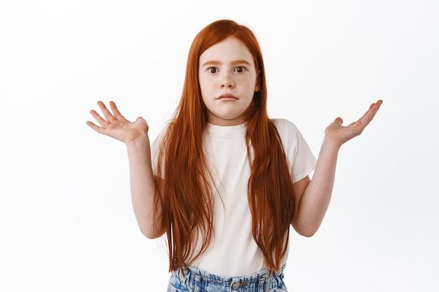 Criança não sabe. garotinha ruiva fofa encolhendo os ombros e levantando as mãos, parece sem noção e confusa na frente, não tem ideia, não consigo entender algo, em pé sobre uma parede branca