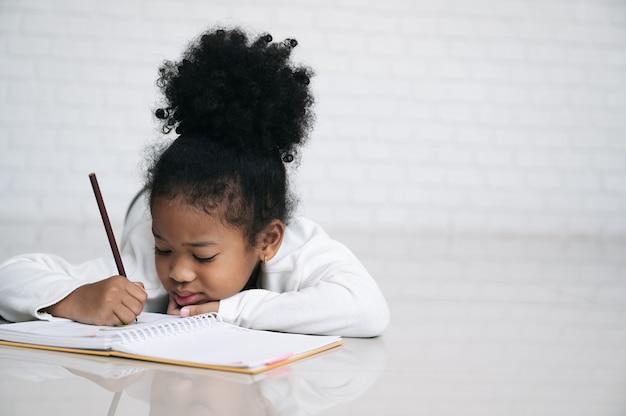 Criança negra com livro no quarto