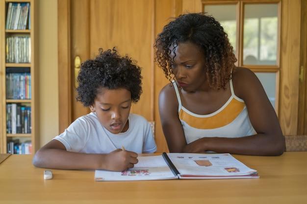 Criança negra faz lição de casa em casa com a atenção de sua mãe. de volta à escola