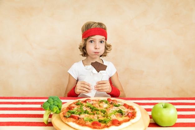 Criança nerd do esportrsman comendo superalimento