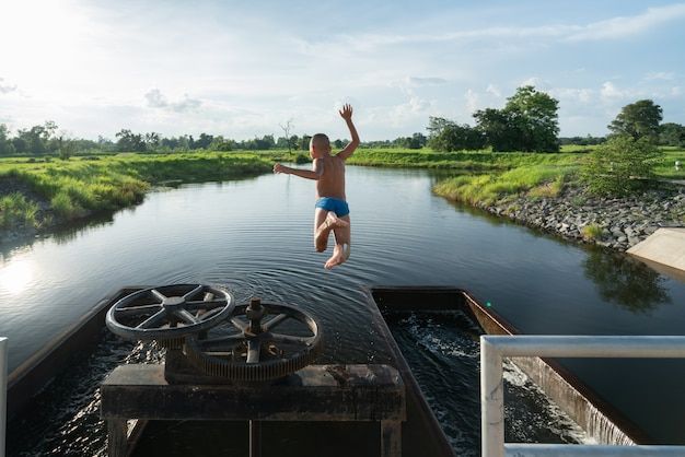 Criança no ar ao saltar no lago com bela sunray - cenário de natureza de verão