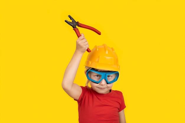 Criança no capacete de construção e óculos com alicate de retenção.