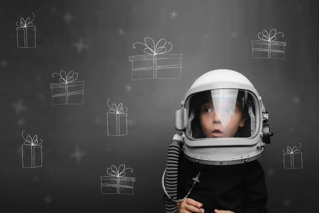 Criança no capacete de um astronauta sonha com o natal e presentes