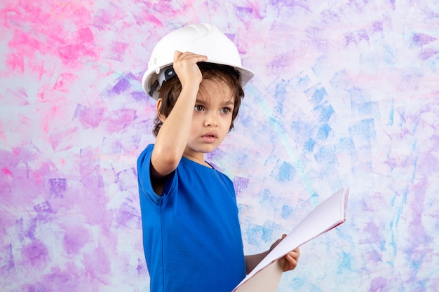 Criança no capacete whtie e camiseta azul, segurando o plano de papel colorido