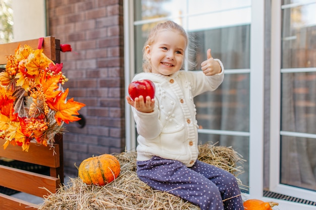 Criança no casaco de malhas brancas, sentado no palheiro com abóboras na varanda e brincando com a maçã.