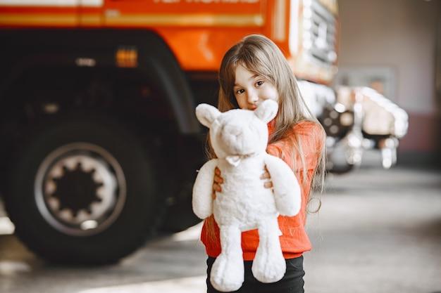 Criança no corpo de bombeiros. menina com um brinquedo. criança perto do caminhão de bombeiros.