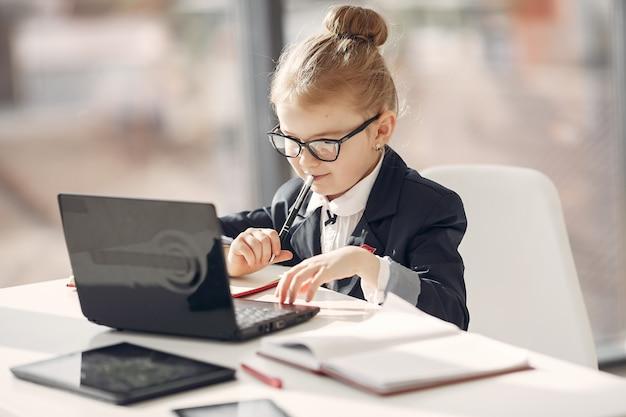 Criança no escritório com um laptop