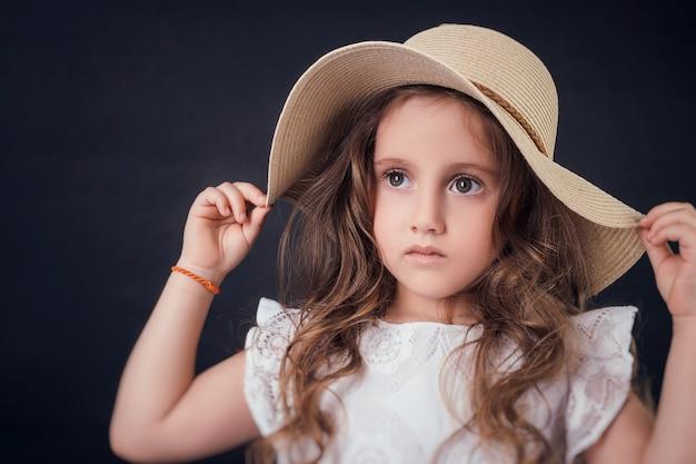 Criança no estúdio posando com roupas da moda