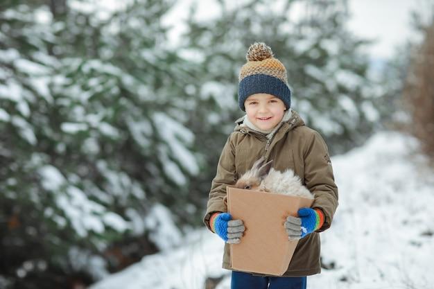 Criança no fundo de árvores cobertas de neve no inverno em um chapéu quente e luvas
