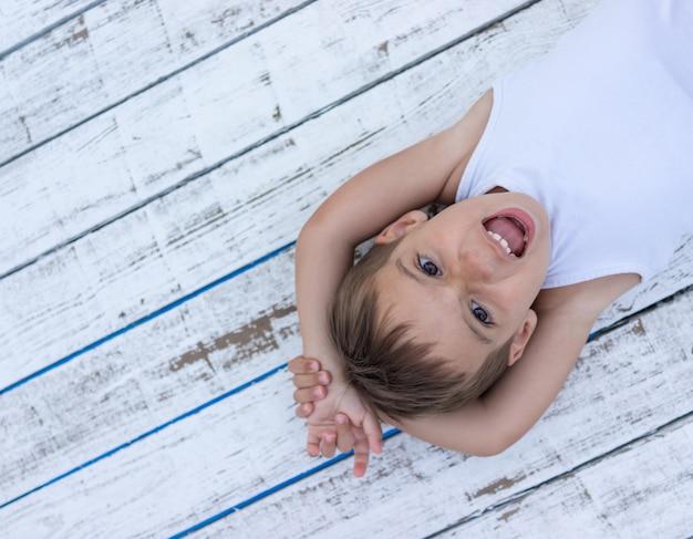Criança no fundo de madeira branca