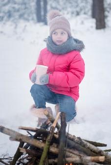 Criança no inverno. uma menina no inverno na natureza bebe chá perto do fogo