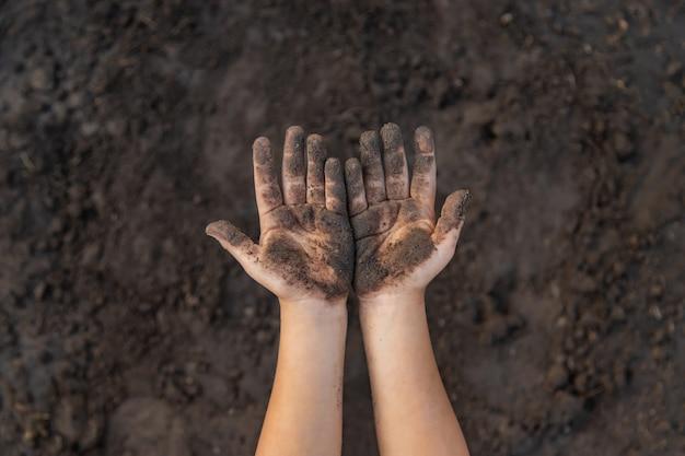 Criança no jardim com a terra nas mãos dela.