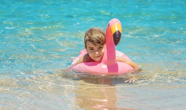 Criança no mar descansando com brinquedo flamingo