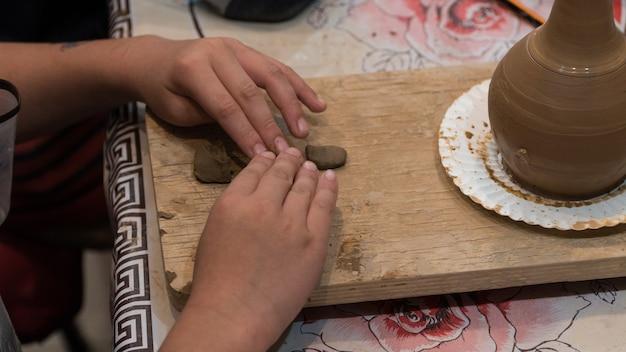 Criança no processo de decorar o pote de barro. estúdio de cerâmica infantil