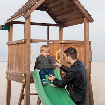 Criança no slide e pai segurando-o