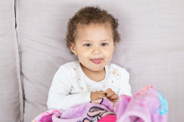 Criança no sofá, mostrando a língua. com coberto.