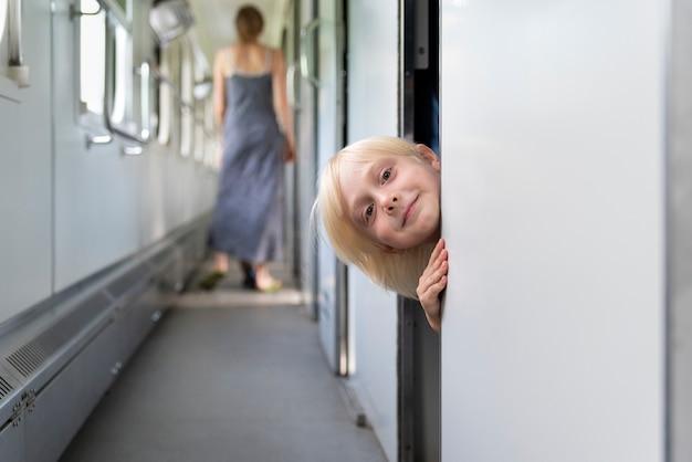 Criança no vagão do trem parece fora do compartimento. garotinho no trem de férias em família.