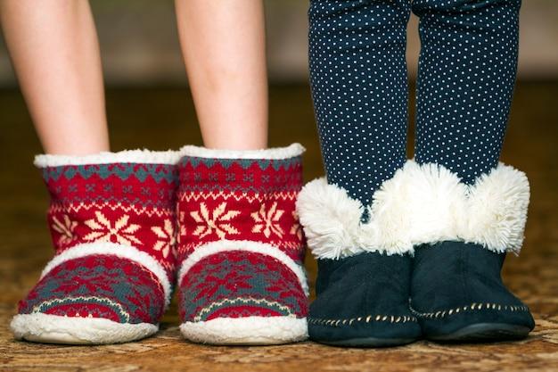 Criança nua pernas e pés em botas de natal de inverno vermelho com padrão de ornamento
