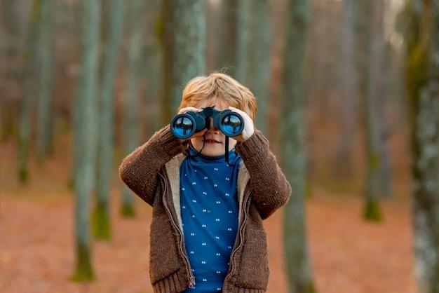 Criança olhando através de binóculos na floresta criança brincando ao ar livre crianças viagens e conceito de aventura