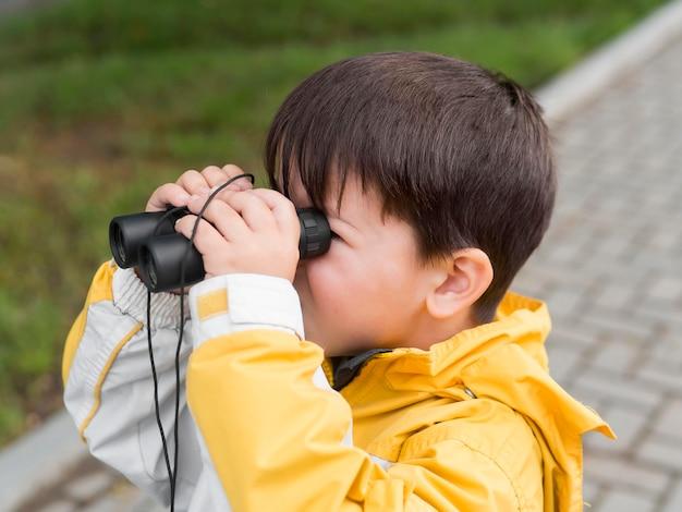 Criança olhando através de binóculos