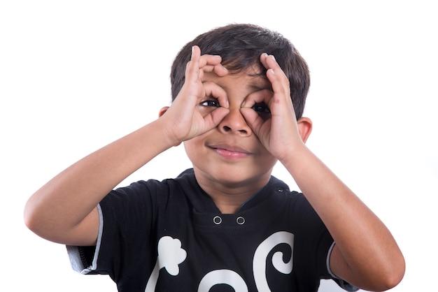 Criança olhando para a câmera através dos dedos em um gesto de ok. imitando binóculos sobre fundo branco