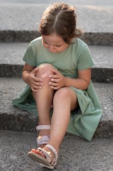 Criança olhando para a lesão no joelho